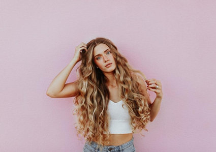 Woman with long curly blonde hair standing in front of a pink wall